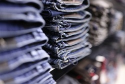 Stack of blue jeans in different shades at store closeup