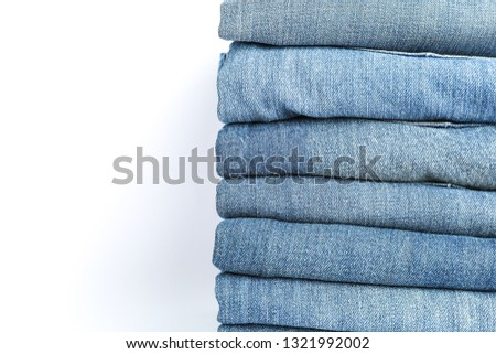 Stack of blue jeans on white background, space for text #1321992002