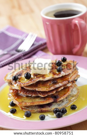 Stack of blueberry pancakes with honey, butter and black coffee