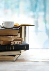 stack of book and Cup of tea on windowsill. concept love of reading, Literature, learning new knowledge, self improvement. text of letters