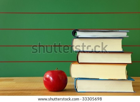 Stack of book and red apple on desk.