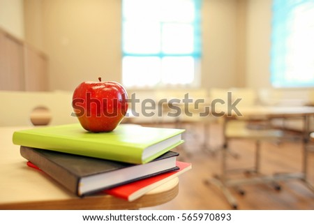 Stack of books and apple on desk at classroom