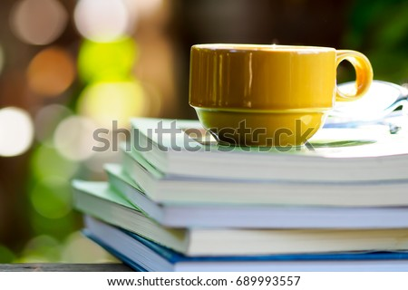 Stack of books and yellow cup of coffee on a green natural background. Coffee in the garden with a book.  Stack of books. #689993557