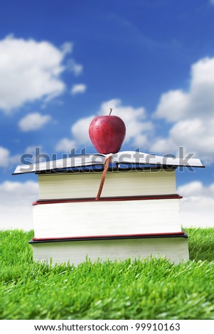 Stack of books in grass for summer reading with red delicious apple on top