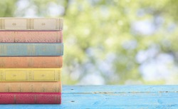 stack of books on blurred nature background