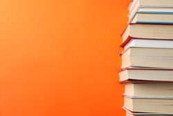 Stack of books on orange background, space for text