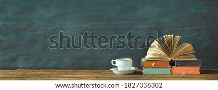 Stack of books, open book and cup of coffee. Reading,literature,education,library,home office concept, panoramic large copy space Foto stock ©
