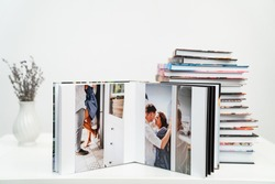stack of books. open photobook from photo shoots of a a beautiful happy couple in the kitchen. grainy paper texture. photo design in the album. Memory. Designer. white background