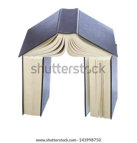 Stack of books shaped as house with walls and roof.