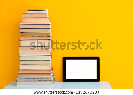 Stack of books versus kindle or tablet for reading, technology innovative education concept on yellow background, copy space