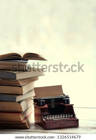 stack of books, vintage typewriter on windowsill. concept love of reading, learning new knowledge, self improvement. cozy still life with book and typewriter. vintage grunge tone. soft selective focus