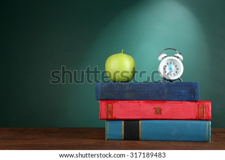 Stack Of Books With Alarm Clock And Green Apple On Chalkboard Background 317189483