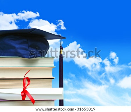 Stack of books with cap and diploma against blue sky