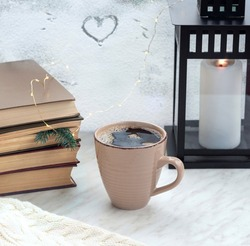 Stack of books with fir branch used as bookmark, big mug with fresh black coffee, lantern with a candle on the windowsill. Window is covered with a snow. Heart drawn on the glass.