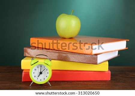 Stack Of Books With Green Apple And Alarm Clock On Desk Chalkboard Background