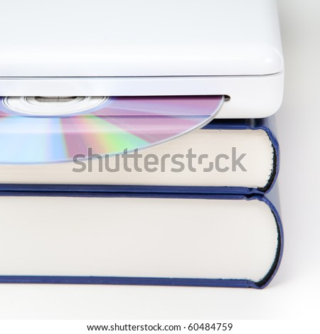 stack of books with laptop computer and CD