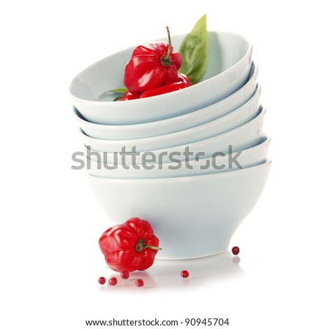 Stack of bowls and red peppers over white