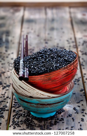 Stack of bowls with black raw rice