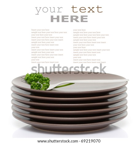 Stack of brown round plates with fork and parsley (with sample text)
