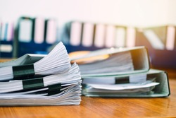 Stack of business report paper file on modern white office desk with bokeh background.