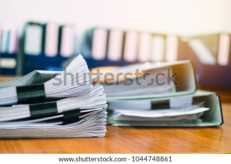 Photo of  Stack of business report paper file on modern white office desk with bokeh background.