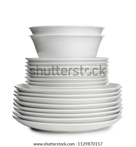 Stack of ceramic dishware on white background #1129870157