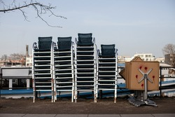 Stack of chairs and tables put together on a street. A pile of street cafe furniture and equipment. Start of tourism season. Stock photography.