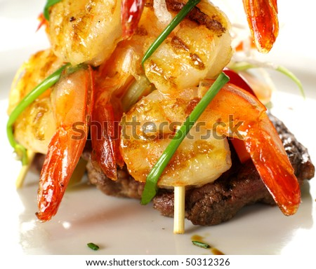 Stack of chargrilled shrimps tied up with chives on top of a grilled steak.