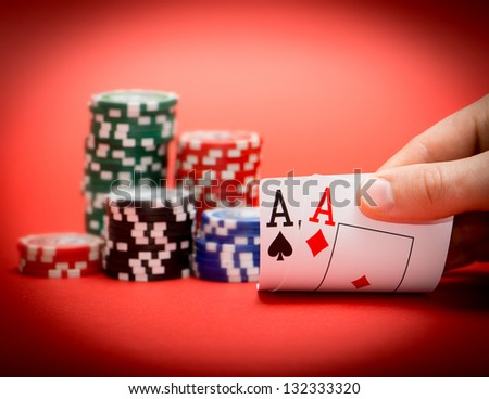 Stack of chips and two aces on a red poker table