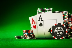 Stack of chips and two aces on the table on the green baize - poker game concept
