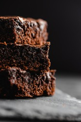 Stack of chocolate brownies on black slate stone background