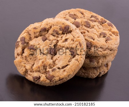 Stack of chocolate chip cookies and cracked chocolate parts isolated on black background