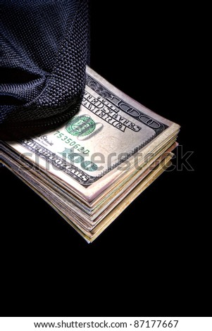 Stack of circulated large denomination US dollar bills sticking out of a canvas bag as a metaphor for under the table cash bribery and illegal hush money corruption in dramatic light over black