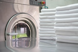 Stack of clean bed sheets in front of industrial washing machine. Focused on washing machines.  Shot taken in the factory.