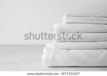 Stack of clean bed sheets on table Photo stock ©