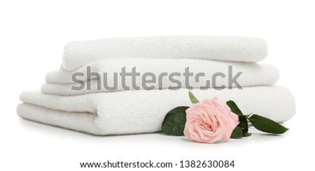 Stack of clean folded towels with flower on white background #1382630084
