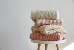 Stack of clean freshly laundered, neatly folded women's clothes on wooden table. Pile of shirts, dresses and sweaters on the table, white wall background. Copy space, close up, top view.
