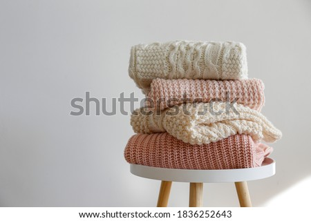 Stack of clean freshly laundered, neatly folded women's clothes on wooden table. Pile of shirts, dresses and sweaters on the table, white wall background. Copy space, close up, top view. Foto d'archivio ©