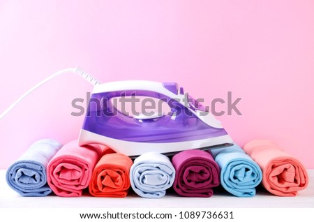 Stack of clean freshly laundered, neatly rolled clothes and electric iron on pressboard. Pile of t-shirts rolls on white wooden ironing board, pink wall background. Copy space, close up, top view. #1089736631