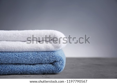 Stack of clean soft towels on table against grey background #1197790567