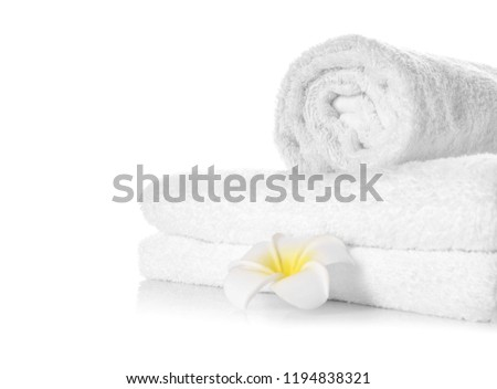 Stack of clean soft towels with flower on white background #1194838321