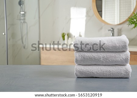 Stack of clean towels on grey stone table in bathroom. Space for text