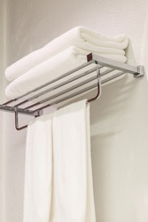 Stack of clean white towels on stainless steel rack in restroom for shower background