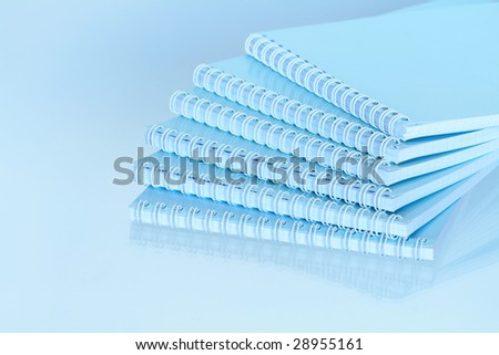 Stack of closed spiral notebooks lying on blue background