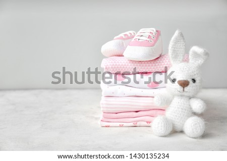 Stack of clothes, shoes and toy on table stock photo