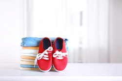 Stack of clothing,baby red textile shoes pair empty copy space background.Child's apparel,clothes and footwear.Shopping.Laundry.Maternity concept.