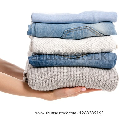 Stack of clothing jeans sweaters in hand on a white background isolation #1268385163