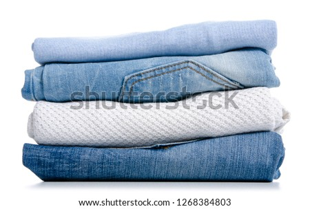 Stack of clothing jeans sweaters on a white background isolation #1268384803