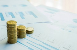 stack of coin on business document graph. Money and financial concepts.
