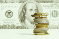 Stack of Coins on Foreground and Blurred One Hundred Dollar Bill on Background, Business and Finance Concept